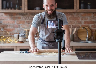 food blogger streaming live. bearded hipster man communicating with subscribers through phone camera. chef rolling out dough with a pin.