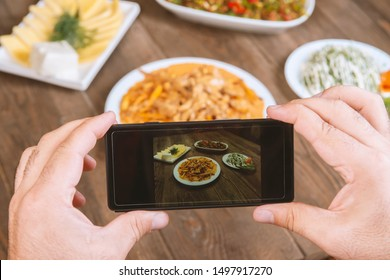 Food blogger using smartphone taking photo .Mans hands make phone photography of Oriental traditional meals. lunch or dinner.Beef stroganoff. For social media, blogging. Top view mobile phone.