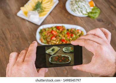 Food blogger using smartphone taking photo .Mans hands make phone photography of Oriental traditional meals. lunch or dinner. For social media, blogging.  Healthy food