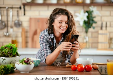 Food blogger using smartphone taking photo. Young woman photographing food in the kitchen.