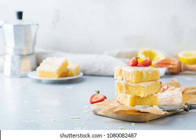 Food, breakfast teatime concept. Homemade lemon polenta cookie bars with white icing on a kitchen table with coffee. Copy space background
