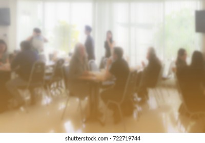 Food canteen cafeteria room in a glass wall of office building with people eating and discuss business, blurred background