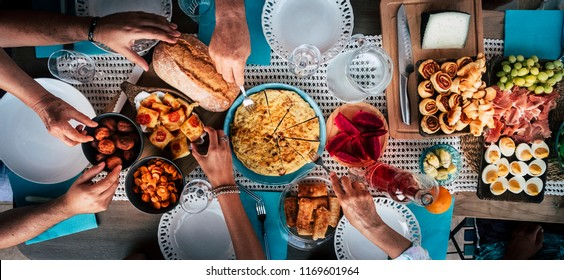 Food Catering Cuisine Culinary Gourmet Buffet Party Concept with lot of hands taking food from various mixed place on the table. having fu. community leisure activity at home or restaurant
