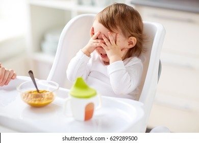 food, child, feeding and people concept - baby with spoon sitting in highchair and eating puree from at home kitchen