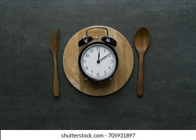 Food clock at lunch time. Healthy food concept on wooden table