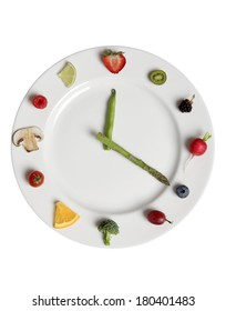 food clock out of vegetables and fruit on white plate with white background