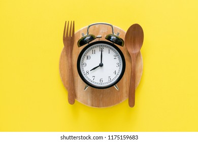 Food clock spoon and fork, Healthy food concept on yellow background