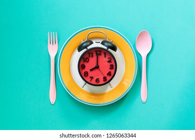 Food clock spoon and fork, Healthy food concept on green background