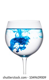 Food coloring diffuse in water inside wine glass area for slogan or advertising text message, on isolated white background.
