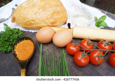 Food composition. Bread, tomatoes, eggs, butter, flour, onion, garlic, parsley, spices.