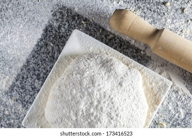 A food composition with pizza dough ready to cook with a wooden kneader / Raw dough pizza