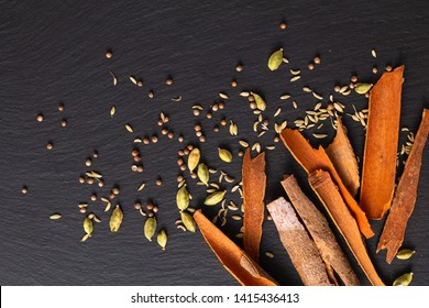 Food concept assortment Oriental spices cardamom pods, coriander seeds, fennel and Cinnamon Cassia Bark Sticks on black slate stone with copy space