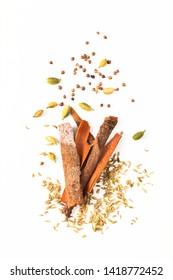Food concept assortment Oriental spices cardamom pods, coriander seeds, fennel and Cinnamon Cassia Bark Sticks on white background with copy space