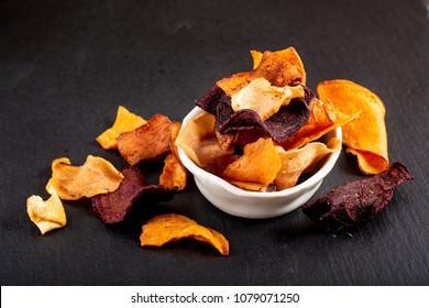Food concept assortment of vegetable chips on black slate plate