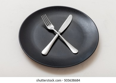 food concept - black plate with crossing knife, spoon on white plastering board