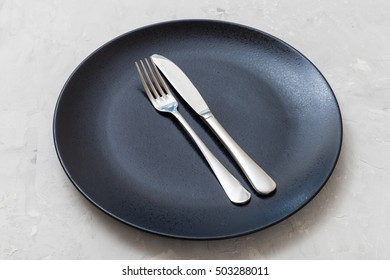 food concept - black plate with parallel knife, spoon on gray concrete surface