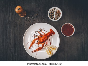 Food concept. Boiled big red fresh crawfish in white plate with lemon slices. Composition with sauce, herbs and pepper grains around. Gray wooden background. Instagram vintage toning effect. Top view.