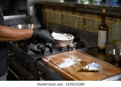 Food concept. The Chef sprinkles flour Fresh Oysters for Roasting in the kitchen. The process of cooking spaghetti with seafood