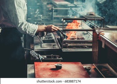 Food concept. Chef in white uniform monitors the degree of roasting and greases with a brush meat with oil sause in interior of restaurant kitchen. Preparing traditional beef steak on barbecue oven.