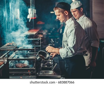 Food concept. Chefs in white uniform monitor the degree of roasting and grease meat with oil in saucepan in interior of modern restaurant kitchen. Preparing traditional beef steak on barbecue oven.
