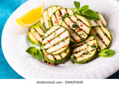 Food concept for a healthy eating summer: grilled zucchini with herbs dressing and olive oil. Soft focus