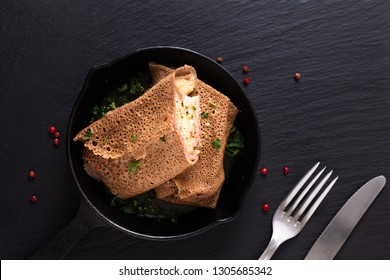 Food concept homemade Ham and Cheese Crepe in iron skillet cast on black slate background