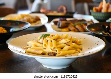 Food concept. Pasta penne with mushroom, bacon and whipping cream on white plate. Blur plates with foods background.