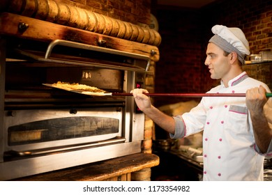 Food concept. Preparing traditional italian pizza. Young chef in white uniform holds in his hands shovel for pizza