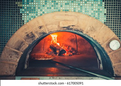 Food concept. Preparing traditional italian pizza. Long shovel for pizza, baking dough in a professional oven with open fire in interior of modern restaurant kitchen