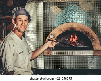 Food concept. Preparing traditional italian pizza. Young smiley chef in white uniform holds in his hand shovel for pizza, he bakes dough in a professional oven in interior of modern restaurant kitchen