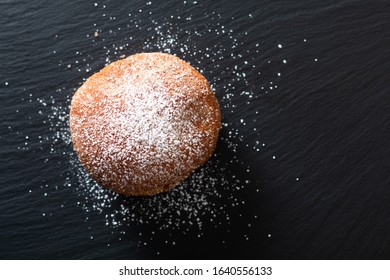 Food concept single Beignet French yeast doughnut deep-fried choux pastry on black slate board background