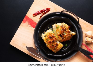 Food concept spot focus homemade butter, garlic, bread crumbs and cheese crunchy Baked cod fish in skillet iron cast pan on black background with copy space