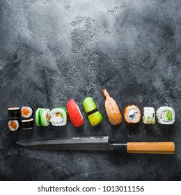 Food concept of sushi, rolls and knife on grey background. Flat lay, Top view