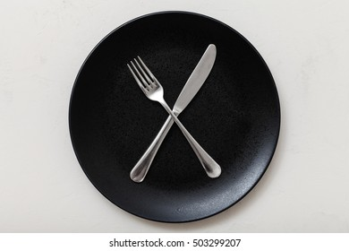 food concept - top view of black plate with crossing knife, spoon on white plastering board