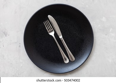 food concept - top view of black plate with parallel knife, spoon on gray concrete surface
