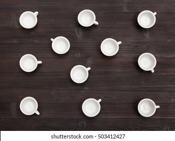food concept - top view of lot of white cups on dark brown board