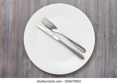 food concept - top view of white plate with parallel knife, spoon on gray brown table