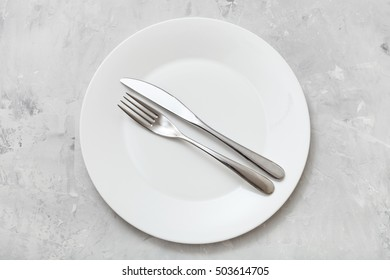 food concept - top view of white plate with parallel knife, spoon on gray concrete surface
