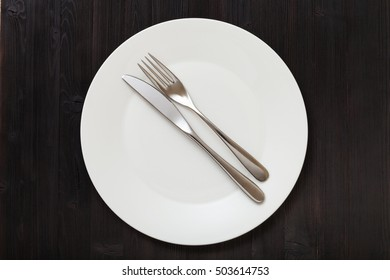 food concept - top view of white plate with parallel knife, spoon on dark brown table