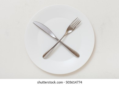 food concept - top view of white plate with crossing knife, spoon on white plastering board