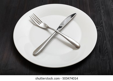 food concept - white plate with crossing knife, spoon on dark brown table