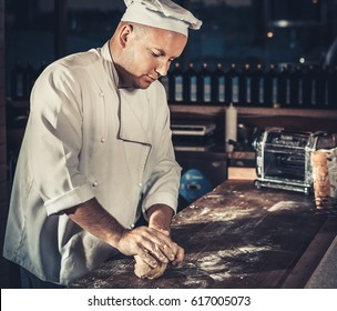 Food concept. Young cheerful chef in white uniform and hat knead the dough on the wooden table in interior of modern restaurant kitchen. Preparing traditional italian pizza