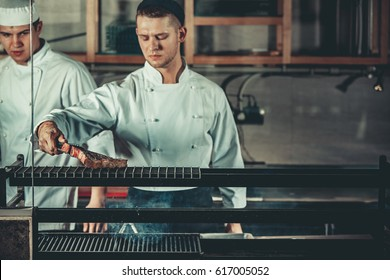 Food concept. Young handsome chef in white uniform monitors the degree of roasting and turns meat with the forceps in interior of restaurant kitchen. Preparing traditional beef steak on barbecue oven.