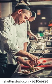 Food concept. Young serious chef in white uniform decorate beef steak meat dish with green herbs and vegetables in interior of modern professional restaurant kitchen. Ready to serve. Ready to eat