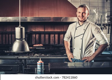 Food concept. Young smiling and handsome chef in white uniform keeps his hands on his belt standing in the interior of modern restaurant kitchen. Preparing traditional beef steak on barbecue oven