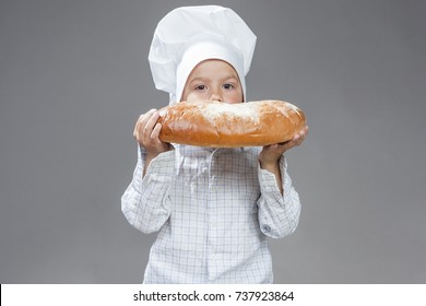 Food Concepts. Portrait of Happy Caucasian Little Boy Eating Big Fresh Bun with Sugar. Posing In Cooking  Hat Agaunst Gray Background. Horizontal Image Composition