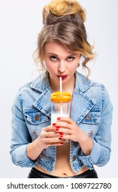 Food Concepts. Young Caucasian Blond Girl Having Fun with Cup of MIlk and Donut Bagel. Drinking Milk Through Straw.Vertical Image Composition