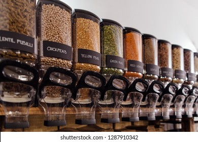 Food containers in zero waste shop filled with raw food products. Package free shop interior - shelf with containers full of peas and lentils in organic shop.