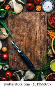 Food cooking background, ingredients for preparation vegan dishes, vegetables, roots, spices, mushrooms and herbs. Vegetable peeler. Healthy food concept. Rustic wooden table background, top view