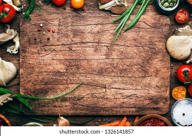 Food cooking background, ingredients for preparation vegan dishes, vegetables, roots, spices, mushrooms and herbs. Old cutting board. Healthy food concept. Rustic wooden table background, top view